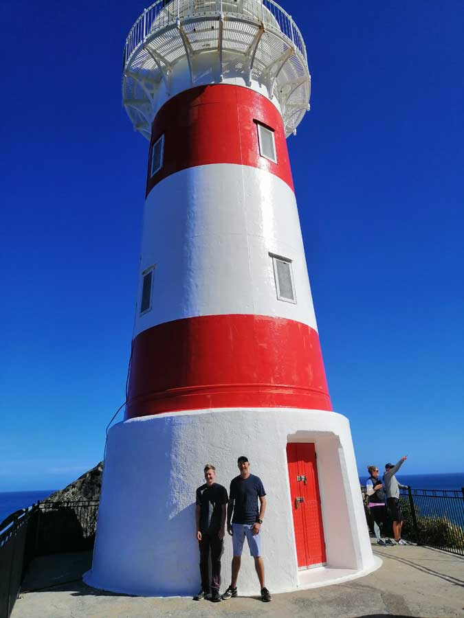two men stand in front of Cape Palliser lighthouse on a sunny day