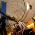 A person with a telescope stargazing at a Carter Observatory dome.