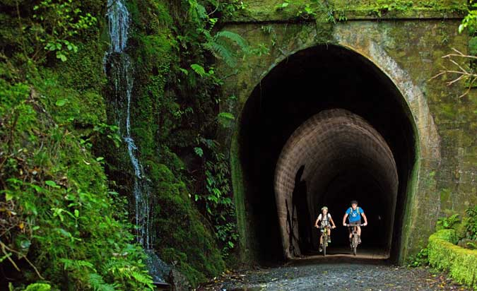 Two cyclists emerging from a tunnel on the Remutaka cycle trail