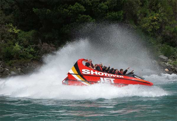 Jetboat in the shotover river with a big spray of water